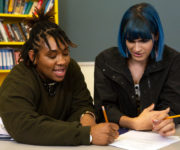 Two non-binary students doing work together in class